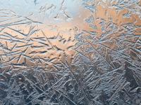 Frozen glass. Ice flowers. Frost flowers. Window frost. Winter in the window. Frozen window. Macro. Soft focus.